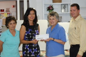 UNITED WAY BOARD VICE PRESIDENT VALERIE MARTINEZ PRESENTS CHECK TO KITCHEN MANAGER SUZAN ROYBAL. ASSISTANT KITCHEN MANAGER MONA ROMERO AND UNITED WAY'S JEREMY VARELA ALSO PICTURED. PHOTO COURTESY RIO GRANDE SUN
